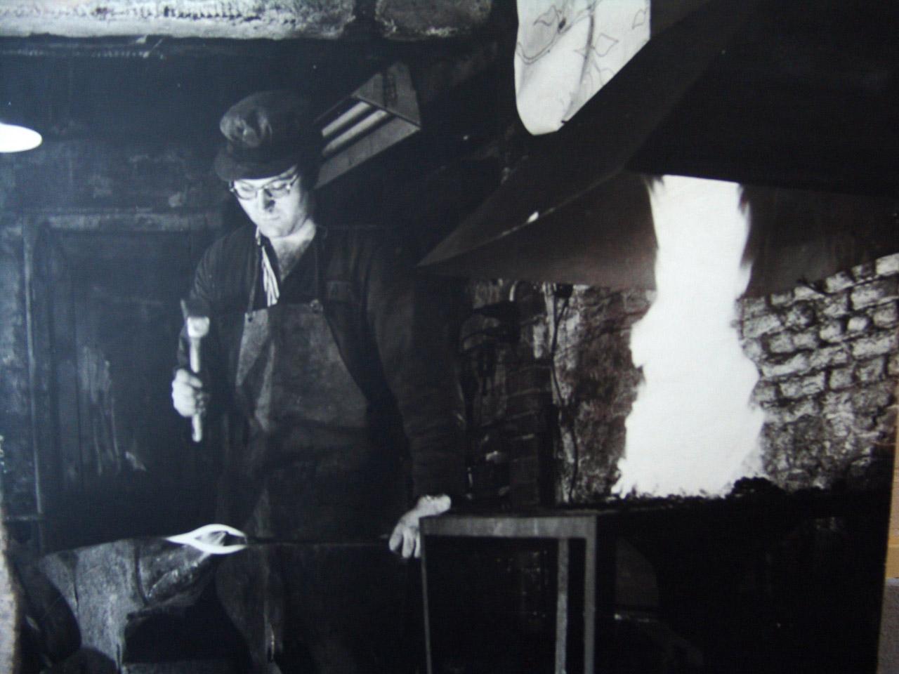 Portretfoto van smid Carino Sunderman bij het aambeeld en het vuur